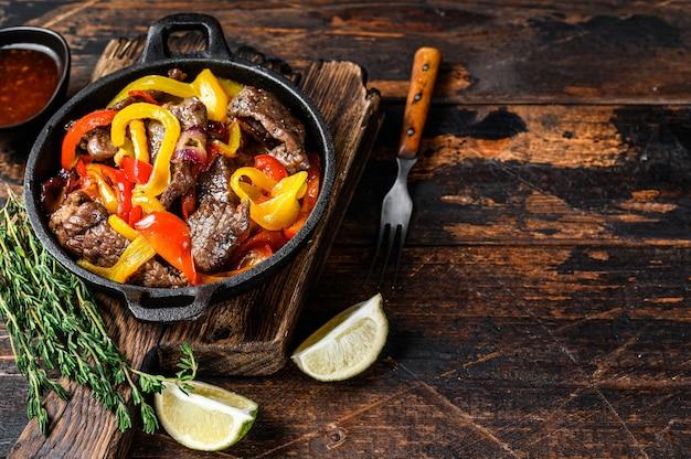 Piatto di cibo messicano tradizionale di carne di manzo fajitas in una padella. tavolo in legno scuro. vista dall'alto.