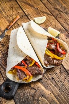 Fajitas tortilla wrap con strisce di carne di manzo, peperone colorato e cipolle e salsa. tavolo di legno. vista dall'alto.