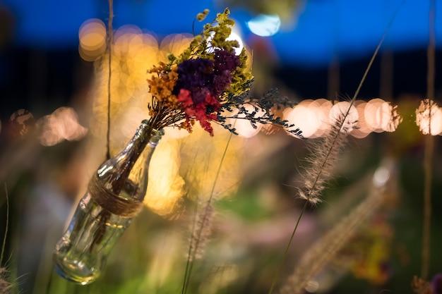 Fiori colorati finti in una bottiglia di vetro soda appesa in giardino con sfondo bokeh chiaro di notte. decorazione esterna di nozze con copia spazio per il testo.