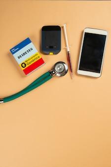 Scatola di medicinali falsi di farmaci per il diabete, stetoscopio, siringa, telefono cellulare e glucometro