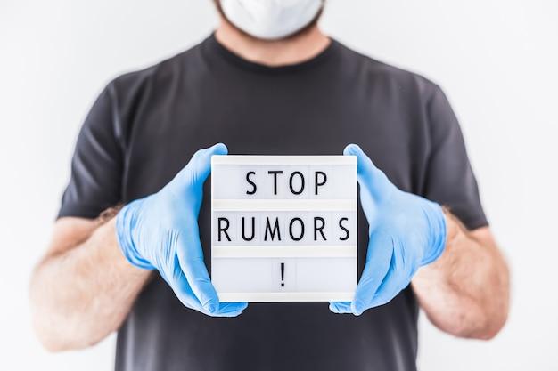 Notizie false durante il concetto di pandemia covid-19. uomo che indossa maschera protettiva e guanti medicali sulle mani che tengono lightbox con testo fermare le voci.
