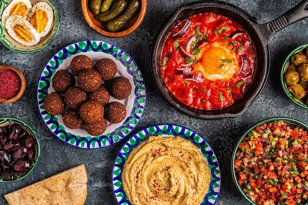 Falafel, hummus, shakshuka, insalata israeliana - piatti tradizionali della cucina israeliana. vista dall'alto.
