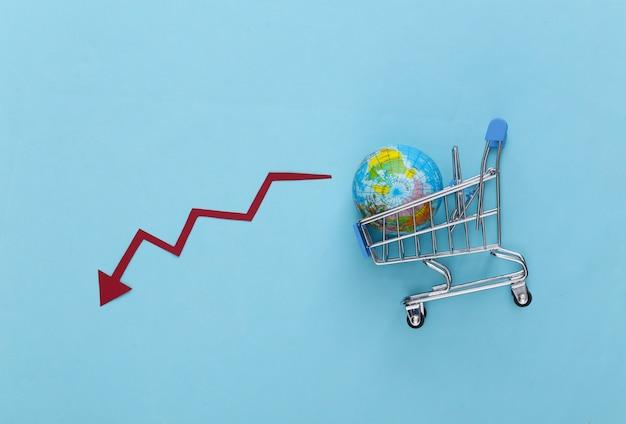 La caduta dello shopping globale. carrello del supermercato con un globo, freccia cadente che tende verso il basso su un blu.