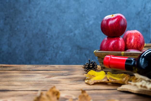 Cornucopia del raccolto autunnale. cesto con mela rossa e vino sul tavolo. copia spazio su uno sfondo di legno nella stagione autunnale.