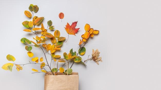 Cadono le foglie in un sacchetto di carta artigianale
