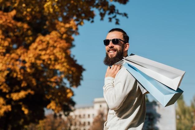 Nuova collezione stagione autunnale ragazzo barbuto hipster con borse della spesa godendo la giornata di sole autunnale