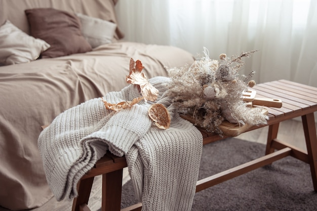 Atmosfera autunnale con dettagli decorativi autunnali e un maglione lavorato a maglia nella stanza.