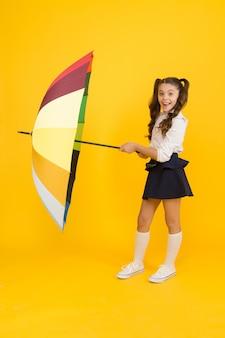 Previsioni meteo autunnali. accessorio di moda. scudo protettivo per ombrellone. ragazza con ombrello. giornata di pioggia passeggiate. infanzia felice. tempo di scuola. stile arcobaleno. vita colorata. scolara felice con l'ombrello.