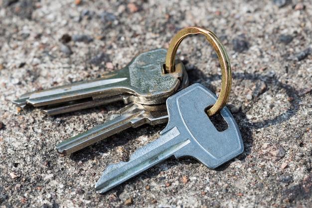 Un mazzo di chiavi caduto giace su una superficie di cemento. foto di alta qualità