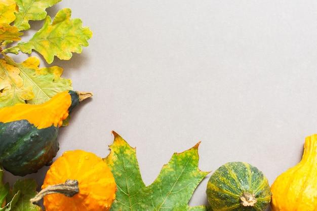 Foglie cadute di alberi e zucche decorative arancioni su sfondo grigio, sfondo autunnale
