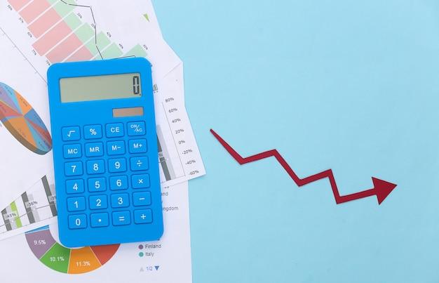 Freccia che cade tendente verso il basso, grafici e tabelle, calcolatrice su un blu. simbolo della crisi globale