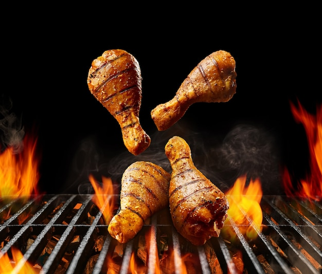 Cosce di pollo alla griglia barbecue che cadono con la crosta dorata e le spezie alla brace ardente...