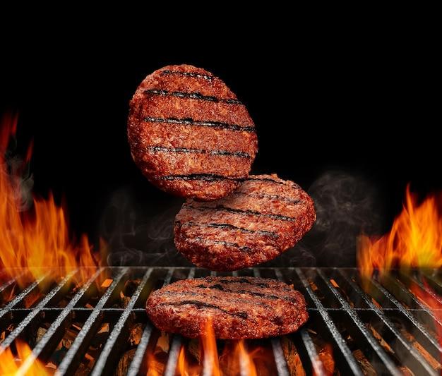 Cotolette di manzo che cadono per hamburger carne arrostita su griglia barbecue in metallo con fuoco fiammeggiante e...