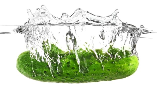 Caduta di cetriolo fresco in acqua contro bianco