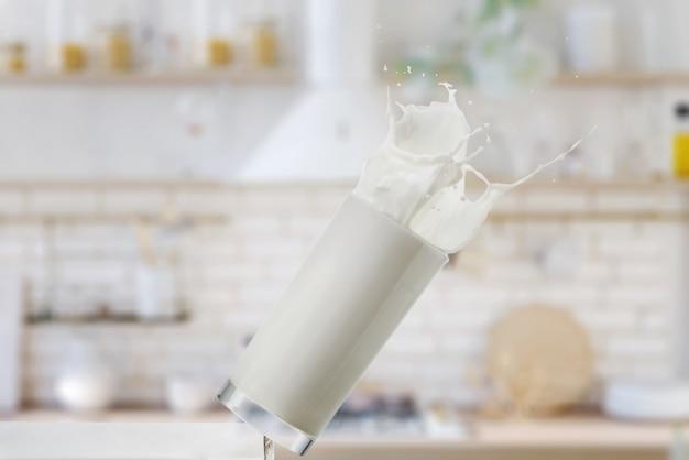 Bicchiere che cade con il latte in cucina