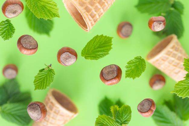Nocciole che cadono con foglie verdi e tazze di wafer per gelato