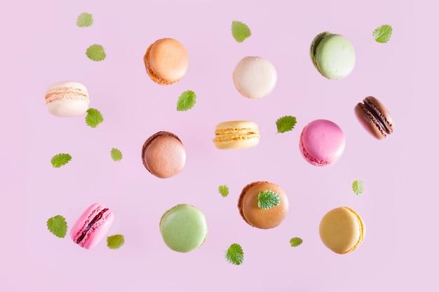 Macarons che cadono con foglie di menta su sfondo rosa