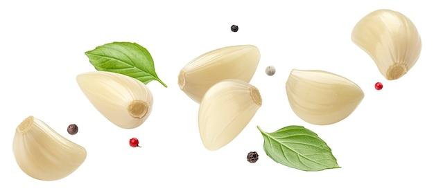 Spicchi d'aglio sbucciati che cadono isolati su sfondo bianco