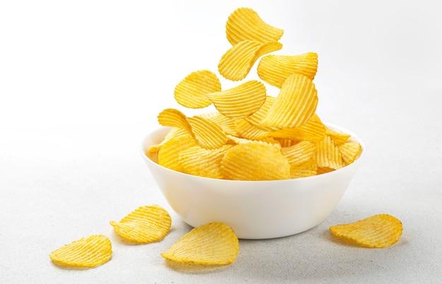 Patatine fritte increspate che cadono in una ciotola bianca isolata su fondo bianco