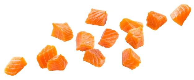 Fette di salmone che cadono isolato su sfondo bianco con tracciato di ritaglio, cubetti di pesce rosso con spezie