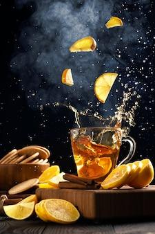 Fette di limone che cadono in una tazza con tè caldo, vapore sale sopra la tazza, schizzi di tè in direzioni diverse