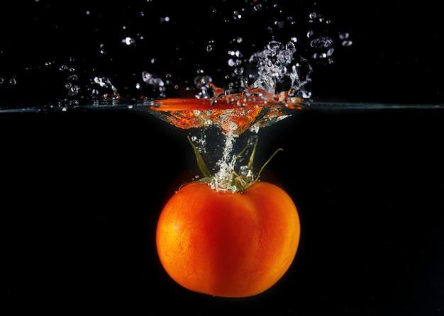 Pomodoro che cade con una coda verde in acqua, spray per design, congelamento in movimento. acqua splash e verdure