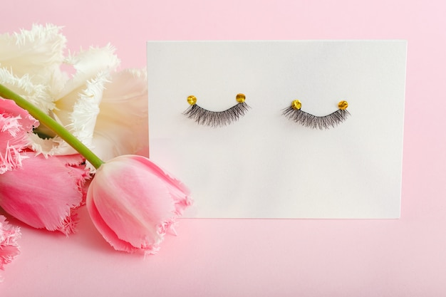 Ciglia finte e composizione di fiori rosa su sfondo rosa. prodotti di bellezza, cosmetici per il trucco degli occhi, estensioni delle ciglia, salone di bellezza o concetto di salone di bellezza spa.