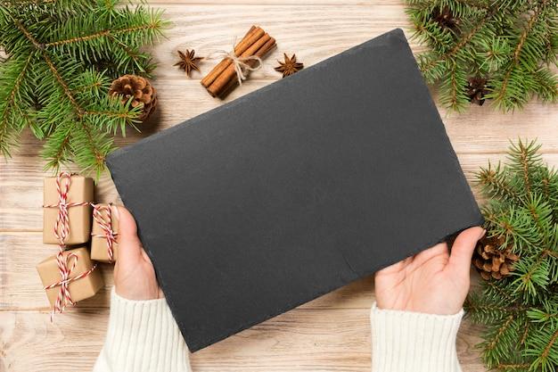 Famale hand hold pietra nera ardesia rotonda su superficie di legno con decorazioni natalizie.