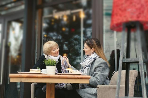 Famiglia, una madre adulta e una figlia si siedono a un tavolo di legno