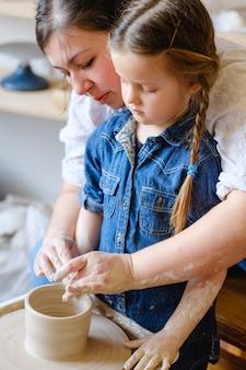 Tempo libero artistico familiare. hobby della ceramica e passatempo artigianale. madre e figlia che lavorano insieme al tornio.