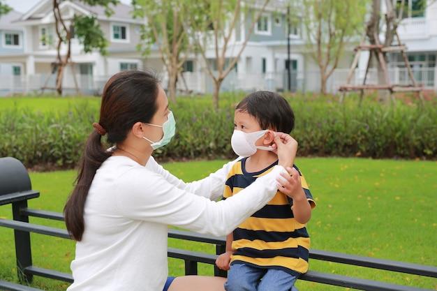 Famiglia mamma asiatica che indossa una maschera protettiva per suo figlio nel giardino pubblico durante l'epidemia di coronavirus e influenza
