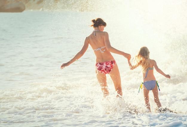 Famiglia sulla spiaggia al tramonto. madre e figlia che corrono insieme.