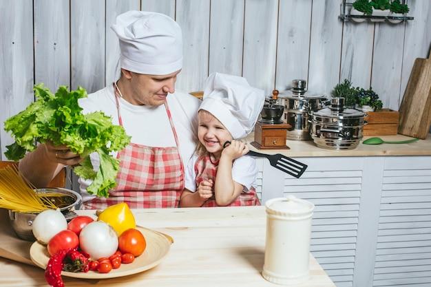 Famiglia, bella figlia papà a casa la cucina ridendo e preparando il cibo insieme