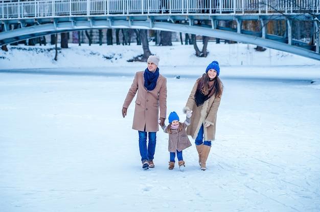 Famiglia in abiti beige e blu divertendosi sul lago ghiacciato nel parco sullo sfondo del ponte