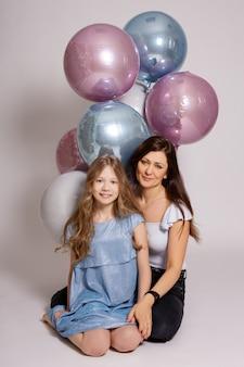 Concetto di famiglia e compleanno - madre e figlia con palloncini d'aria pastello seduti su sfondo bianco