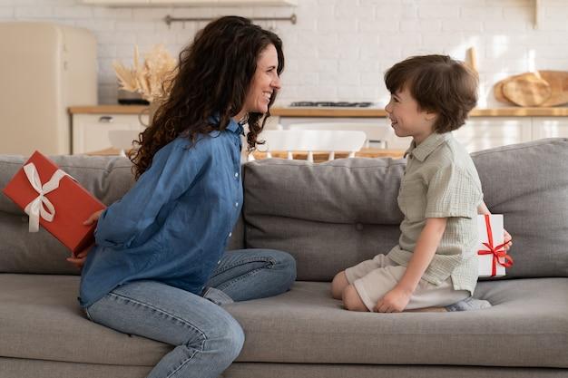 Sorpresa di compleanno di famiglia eccitata madre e bambino che nascondono scatole regalo si siedono sul divano a scambiarsi regali