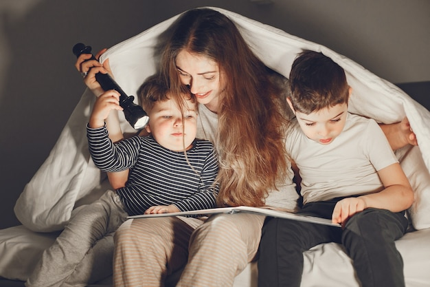 Famiglia sotto le coperte a letto leggendo un libro.