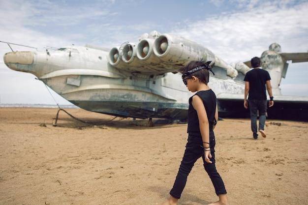 Famiglia un ragazzo e suo padre in abiti rocker camminano su un aereo ekranoplan abbandonato