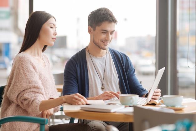 Affari di famiglia. bella giovane coppia che lavora al computer portatile durante la pausa pranzo mentre è seduto alla caffetteria.