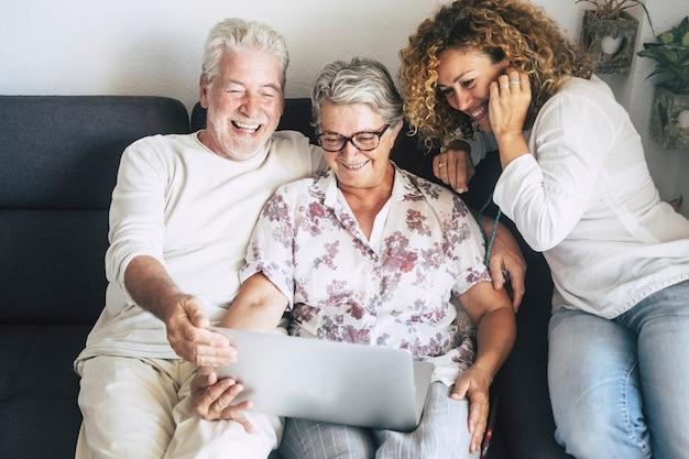 Persone di famiglia cacuasiane in attività per il tempo libero di tecnologia indoor a casa utilizzando laptop e divertirsi eith internet o chat video con amici o genitori insieme in amicizia persone moderne computer