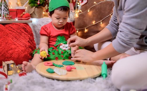 La famiglia festeggia il natale e il felice anno nuovo a casa. stile di vita di mamma e bambino durante le vacanze di fine anno.