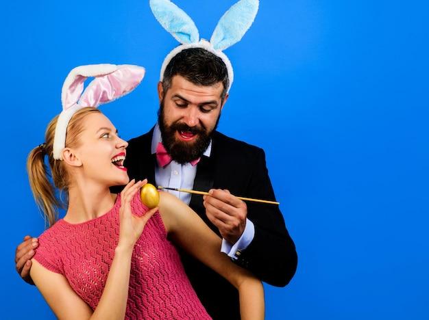 La famiglia celebra la pasqua. happy bunny coppia pittura uova. decorare l'uovo. vacanze di primavera.
