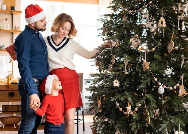 Famiglia che celebra il natale insieme accanto all'albero