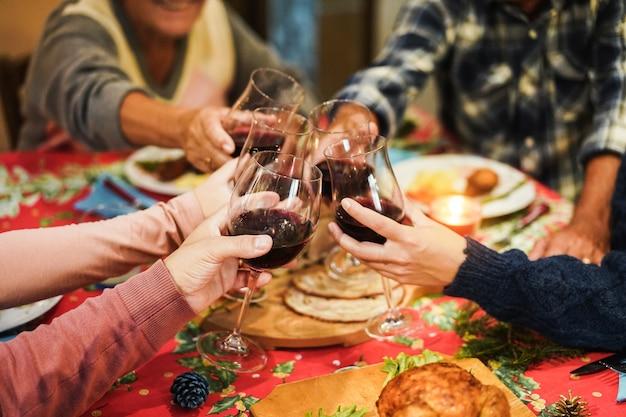 Famiglia tifo con vino rosso mentre mangia la cena di vacanze di dicembre insieme
