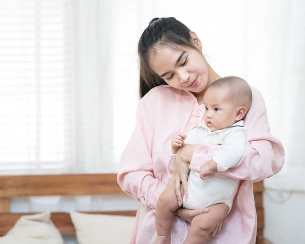 Concetto della famiglia, del bambino e di paternità - abbracciare sorridente della bella giovane madre asiatica felice che tiene neonato nelle sue armi a casa.