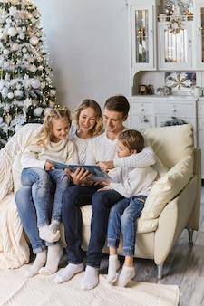 Famiglia, infanzia, vacanze e persone - madre, padre e bambini sorridenti che leggono un libro su sfondo di luci