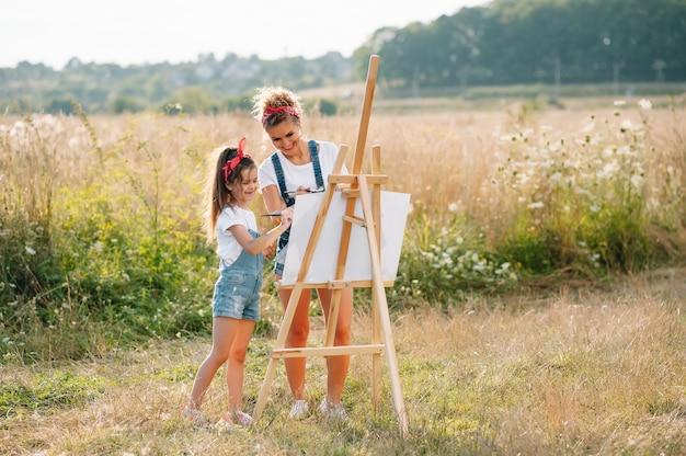 Concetto di famiglia, bambini e persone - madre felice e figlia che disegnano e parlano sopra la superficie verde