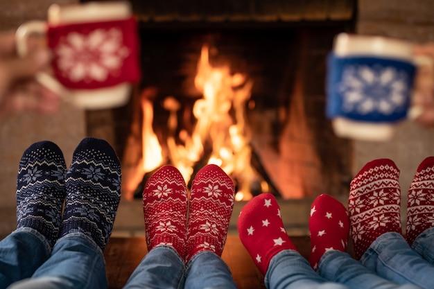 Famiglia in calze di natale vicino al camino madre, padre e figli si divertono insieme