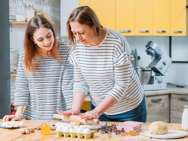 Hobby di cucina familiare. figlia che guarda sua madre stendere la pasta, mentre prepara i biscotti di pan di zenzero