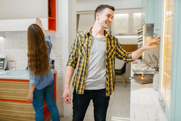 Coppia di famiglia acquisto di mobili da cucina nello showroom del negozio di mobili. uomo e donna che cercano un assortimento in negozio, marito e moglie acquistano beni per interni domestici moderni